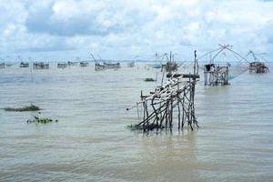 Paysage marin avec des outils de pêche traditionnels bondés dans la mer avec des toits en arrière-plan photo