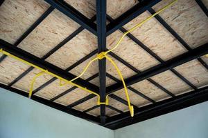 les tuyaux électriques jaunes en cours d'installation sur la structure du toit en acier