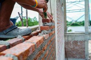 travailleur utilise la truelle pour installer les briques rouges sur le mur