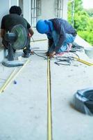 travailleurs installant le fil électrique et le tuyau dans la maison en construction