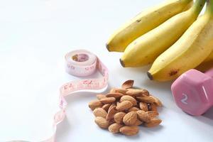 plan de régime avec des amandes, des haltères et de la banane sur la table photo