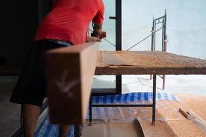 Retour portrait de menuisier tient un outil électrique frottant la surface du bois pour la menuiserie sur le chantier de construction photo
