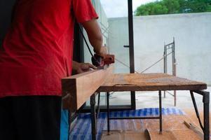 Gros plan main de charpentier tient un outil électrique frottant la surface du bois photo