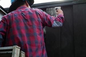Focus sur la main du travailleur peinture couleur noire sur la clôture en acier photo