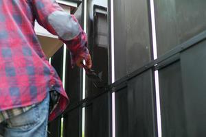 Mouvement main floue du travailleur peinture couleur noire sur la clôture en acier photo