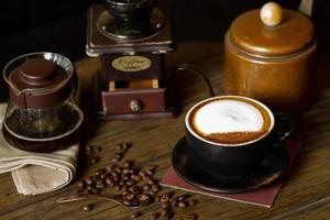 Vue de dessus gros plan de la tasse de cappucino chaud avec mise au point sélective sur les grains de café sur la table en bois avec fond de moulin flou