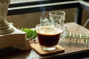 Verre gros plan de café noir chaud avec de la fumée sur la table en bois photo