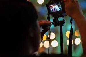 Mains de touriste enregistrant la vidéo par la caméra sur le trépied avec des lumières bokeh scintillantes en arrière-plan photo