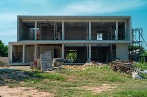 Paysage et perspective de maison en construction avec des tas de matériaux et équipements avec ciel bleu clair en arrière-plan photo