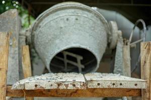 Mise au point sélective sur le groupe de pierres écrasées sur la plaque d'acier avec bétonnière floue