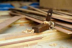 Gros plan mise au point sélective sur l'affûteur en bois vintage de charpentier pour frotter le bois. l'outil traditionnel de bricoleur sur le tas de bois avec de la sciure de bois photo
