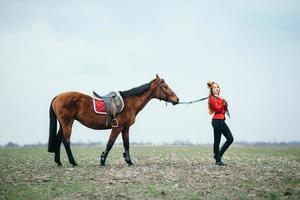 Fille jockey aux cheveux roux dans un cardigan rouge et des bottes noires avec un cheval
