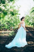 fille brune dans une robe turquoise dans le jardin de printemps