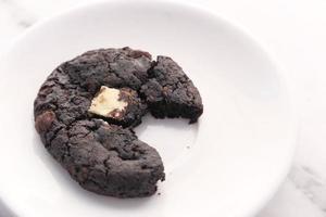 Biscuit au chocolat à moitié mangé sur une assiette