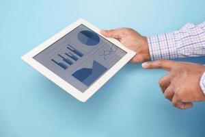 La main de l'homme travaillant sur tablette numérique sur fond bleu