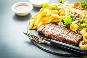 Steak de viande de bœuf grillé avec frites rondelle d'oignon avec sauce et légumes frais