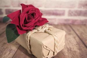 fleur rose sur une boîte cadeau en papier brun