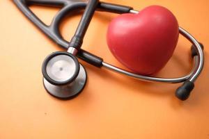 symbole de forme de coeur et stéthoscope sur fond orange photo