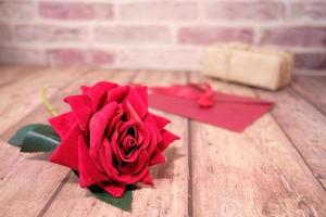 rose rouge et cadeaux de la saint-valentin sur table en bois