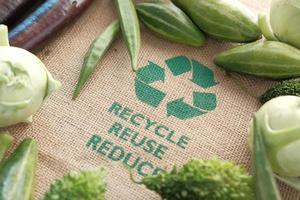 Sac à provisions réutilisable avec signe de flèches recyclées et légumes sur table