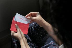 personne ouvrant une carte de remerciement photo