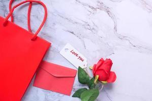 Vue de dessus du coffret cadeau, enveloppe et fleur rose sur fond blanc