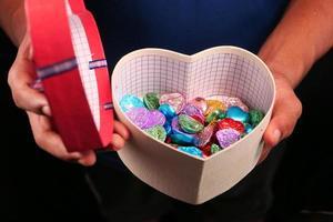 boîte-cadeau en forme de coeur avec des bonbons isolé sur fond noir photo