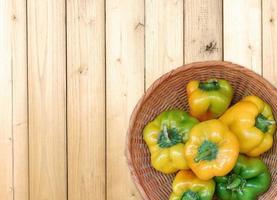 Poivrons jaunes et verts dans un bol en osier sur un fond de table en bois photo