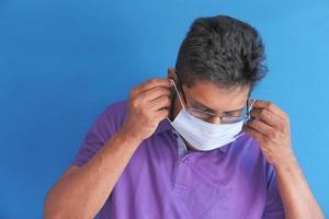 homme portant un masque facial sur fond bleu