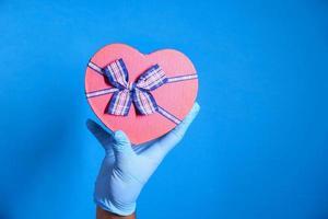 main sur une boîte cadeau en forme de coeur rouge photo