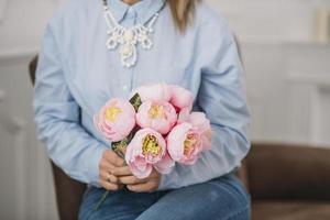 femme en bleu tenant des pivoines roses photo