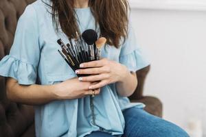 femme tenant des pinceaux de maquillage
