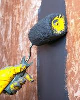 Peinture à la main mur de la maison avec de la peinture acrylique grise avec un rouleau en gants de travail jaunes photo