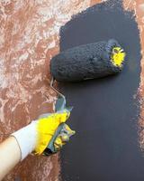 Mur de maison peint à la main avec de la peinture acrylique grise avec un rouleau en gants de travail jaunes photo