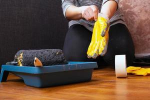 peintre de travail met des gants. outils pour les réparations à domicile, la peinture murale photo