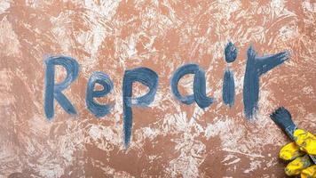 écrit sur le mur le mot réparation et un pinceau à la main photo