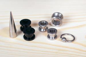 Tunnels piercing et étirement d'oreille sur un fond en bois close-up photo