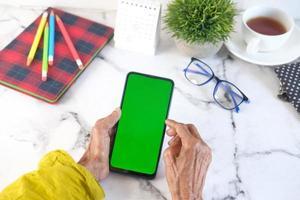main de femmes âgées à l'aide de téléphone intelligent avec écran vert photo