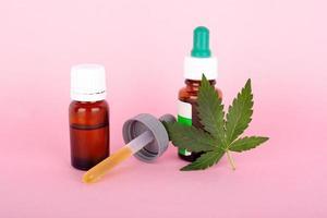 concept de marijuana médicale avec feuille de cannabis et pipette sur fond rose photo