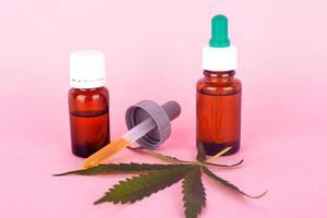 Huile de chanvre à usage médical, bouteilles avec extrait de cannabis médical sur fond rose photo