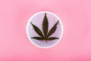 Concept de cosmétiques, de beauté et de soins de la peau de marijuana biologique naturelle sur fond rose photo