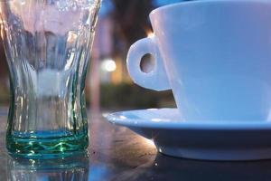 Délicieuse tasse à café et tasse en verre isolé sur fond marron photo