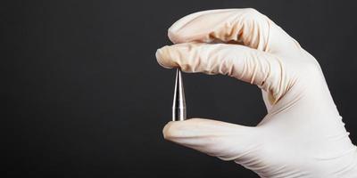 La main dans un gant jetable blanc tenant un extenseur d'oreille piercing photo
