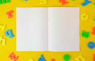 a ouvert un cahier de deux pages sur fond jaune couvert de lettres. concept d'éducation. Copiez le papier de l'espace pour la photo et le message texte.