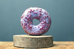 Donut avec glaçage violet sur un support en bois sur fond gris photo