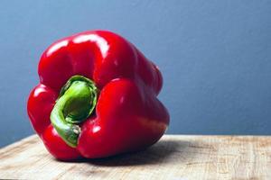 Doux gros poivron rouge sur fond gris avec espace copie photo