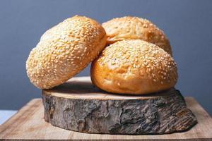 Petits pains pour faire des hamburgers aux graines de sésame sur un support en bois sur fond gris photo
