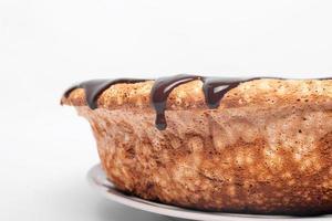 Chocolat qui coule sur les côtés du gâteau sur fond blanc