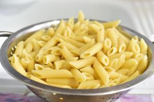 Pâtes italiennes fraîchement lavées dans une passoire dans la cuisine photo