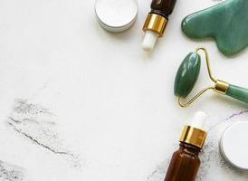 Massage du visage rouleau de jade avec produit cosmétique sur fond de marbre blanc photo
